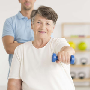 Elderly woman doing active, isometric exercises guided by physical therapist at the hospital rehabilitation center