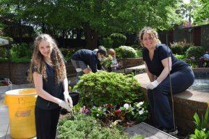 women working in plant garden near fountain