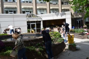 people working on plant garden in front of building