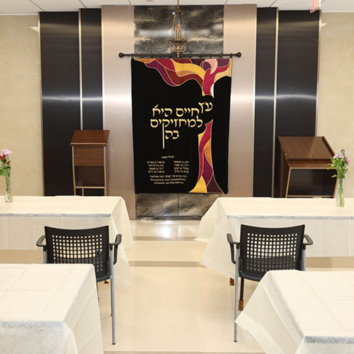 white tables and black chairs in front of hebrew display