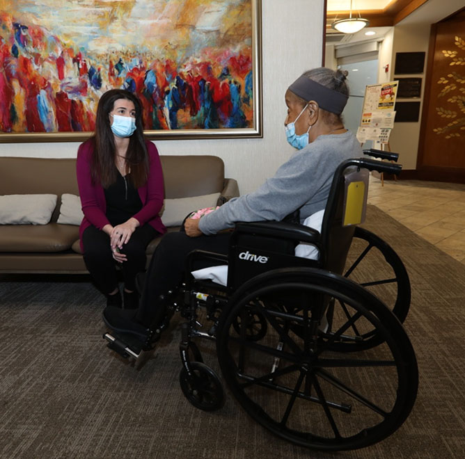Woman and man in wheelchair in Margaret Tietz lobby